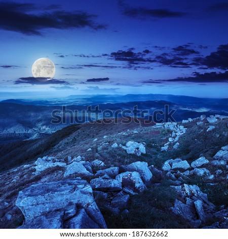 white sharp stones on the hillside at night in moon light - stock photo