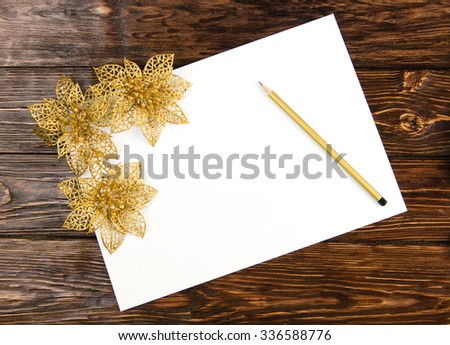 white sheet of paper with a pencil and gold flowers on a wooden background - stock photo