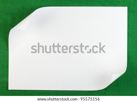 White sheet of paper with curled edge on green background - stock photo