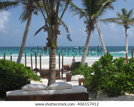 White sheets day bed under the shade of palm trees on a tropical Caribbean beach