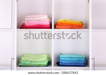 White shelves with colored clothing close up - stock photo