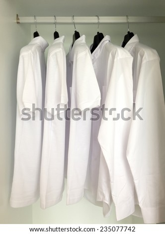 white shirts hanging on cloths racks - stock photo