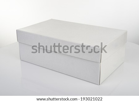 White shoe box isolated on white table with reflection - stock photo