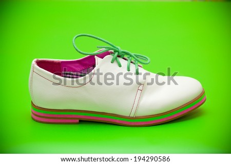 white shoes with green shoelaces on a green background - stock photo