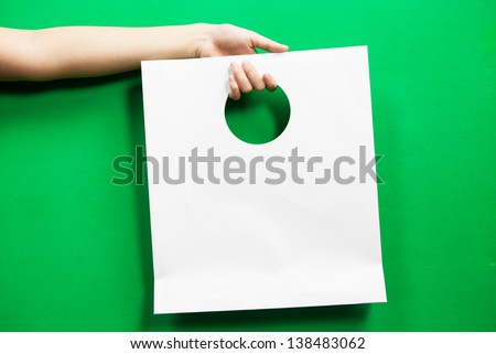 white Shopping bag  on green background - stock photo