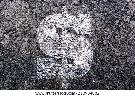 White sign dollar on asphalt - stock photo