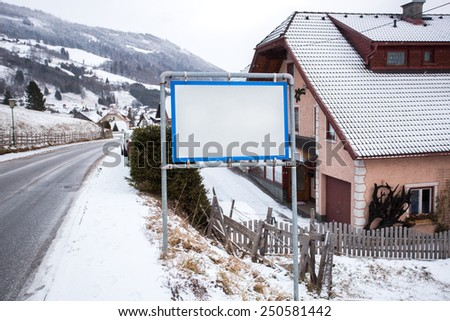 White signpost with copy space in Austrian village at mountains - stock photo
