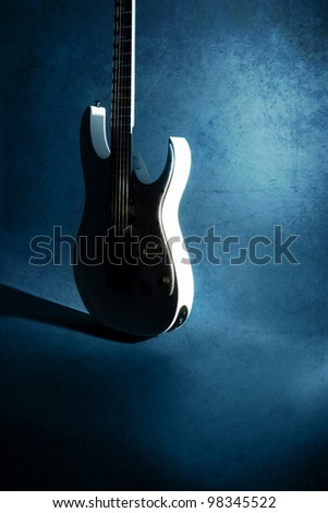 white silhouette of guitar on grunge blue background - stock photo