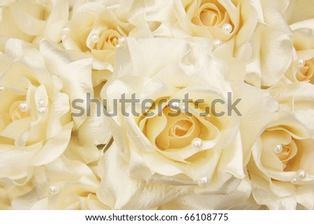 White silk roses with cream pearls. Shallow dof, focus on the center blossom. - stock photo