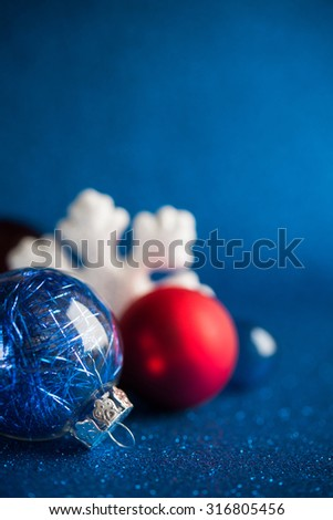 White, silver and red christmas ornaments on dark blue glitter background with space for text. Merry christmas card. Winter holidays. Xmas. - stock photo
