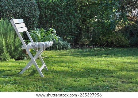 white single chair on the grass in a countryside garden  - stock photo