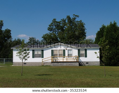 White single-wide mobile residential low income home with vinyl siding on the facade. - stock photo