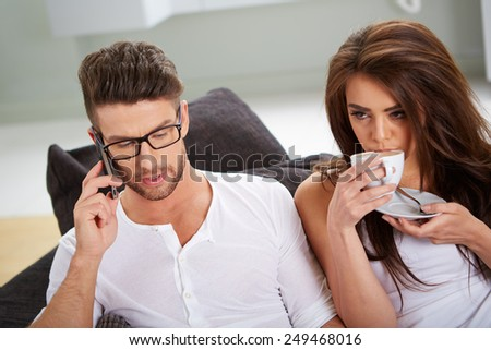 White Sitting Couple in Casual Clothing Having Coffee, with mobile phone - stock photo