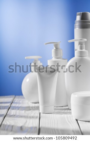 white skincare items on wooden table - stock photo