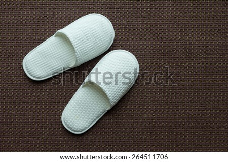 White slippers on brown carpet - stock photo