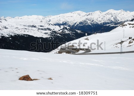 White slope with streamer of road against black-and-white mountain ranges snow-covered from above and azure sky - stock photo