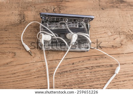 White small plastic mini Earphones and cassette tape player on old retro vintage aged wooden texture background Idea concept symbol audio book - stock photo