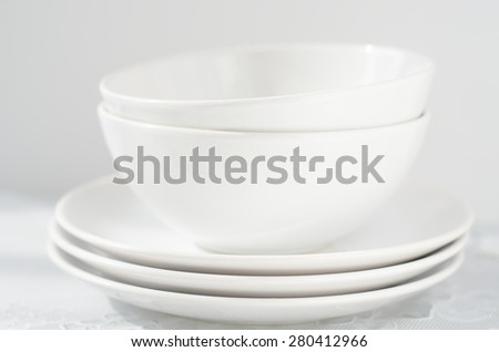 white small plates and bowls on a light table - stock photo