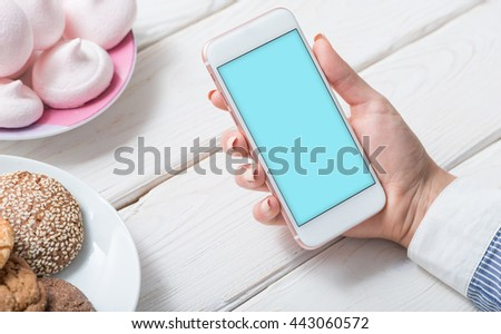 White smart phone in woman's hand over cafe desktop. Clipping path included.