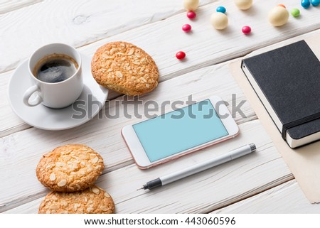 White smart phone on a cafe desktop among cookies with coffee cup. Clipping path included.