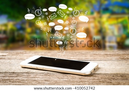 White smart phone on a wooden table emitting holographic image of social media related icons. Blurred city background. - stock photo