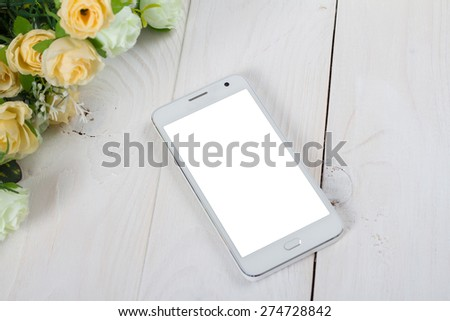 White smart phone with blank screen lying on wooden table - stock photo