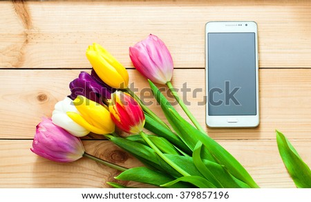 White smart phone with bouquet of tulips on wooden board. - stock photo