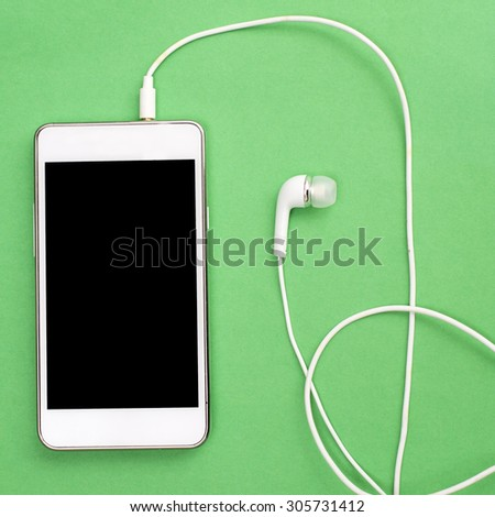 White smart phone with earphones and isolated screen on green, from above - stock photo