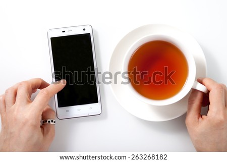 White smartphone and a cup of tea on white glass table and woman hands holding cup and touching the touchscreen - stock photo