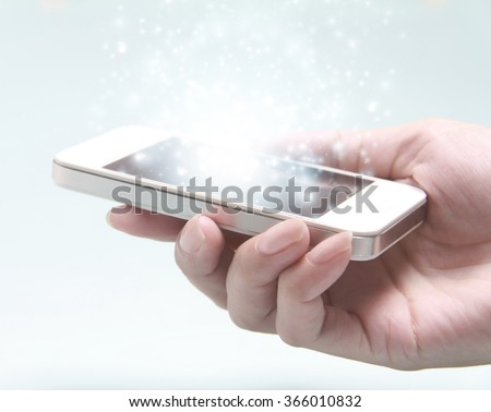 White smartphone with hand isolated on light background. A smartphone is a mobile phone with highly advanced features.