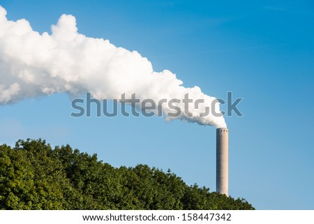 White smoke and steam from a high chimney of a power plant against a bright blue sky and above concealing trees. - stock photo