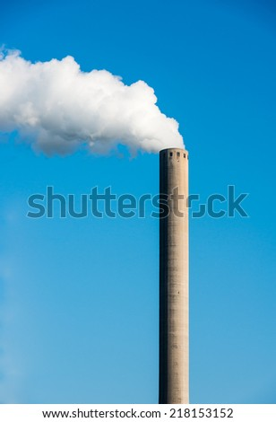 White smoke clouds from a high concrete chimney against a clean blue sky on a sunny day in the summer season.