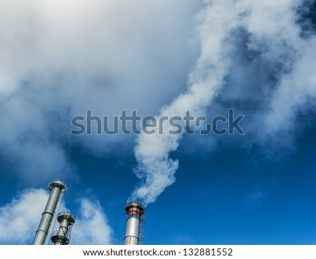 White smoke from coal powered plant stacks, profiled on bright blue sky - stock photo