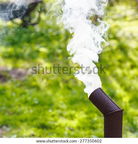White smoke from the chimney of a samovar on backyard - stock photo