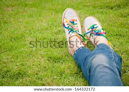 white sneakers on girl legs on grass during sunny serene summer day. - stock photo