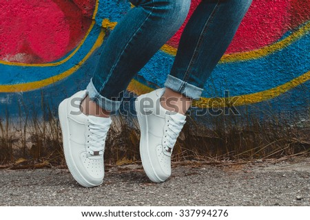 White sneakers on girl legs on the graffiti background - stock photo