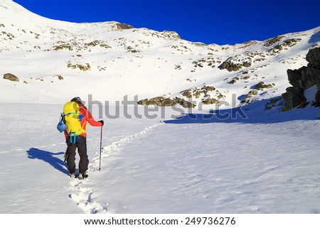 White snow field and backpacker following a foot step trail  - stock photo