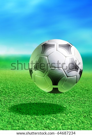 white soccer ball on green ground in motion - stock photo