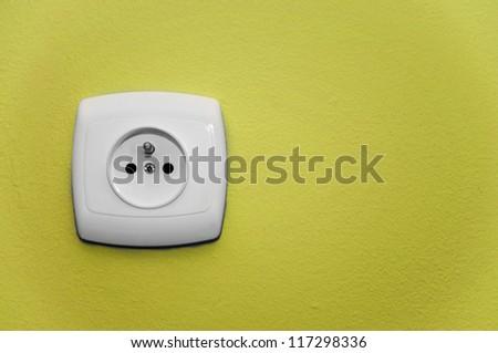white socket on a yellow wall - stock photo
