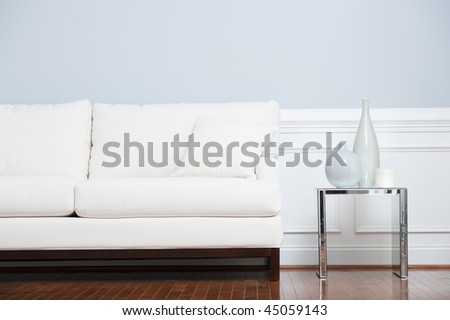 White sofa and glass end table with vases set against pale blue wall. Horizontal shot. - stock photo
