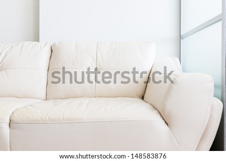 white sofa near glass partition and white wall