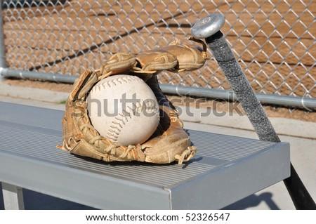 White Softball, Bat, and Glove on an Aluminum Bench - stock photo