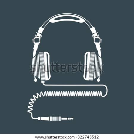 white solid color dj headphones with coiled cord and jack connector dark background  - stock photo
