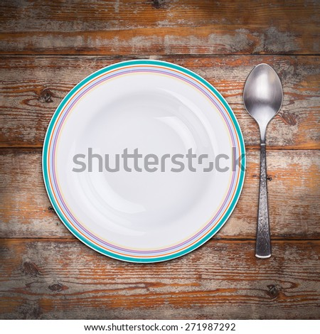 White soup plate on old wooden table - stock photo