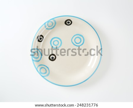 White soup plate with black and blue circles and blue trim