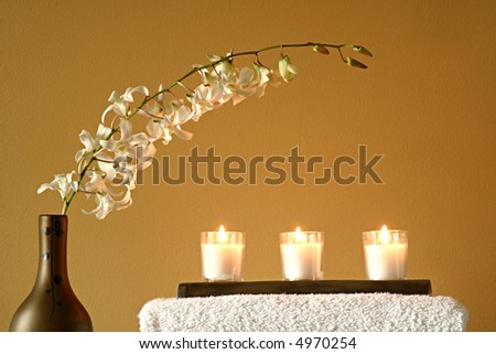 White Spa Towels with Candles and Flowers in Vase - stock photo
