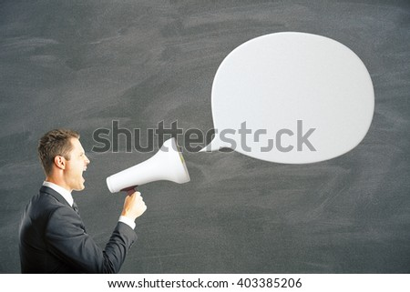 White speech bubble and caucasian businessman shouting into megaphone. Mock up - stock photo