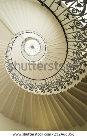 White spiral staircase with a black fence. - stock photo