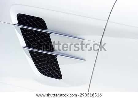 White sport car bodywork, metallic surface of racing vehicle, concept of aerodynamic high speed transport body, detail of door, wing and air intake  - stock photo