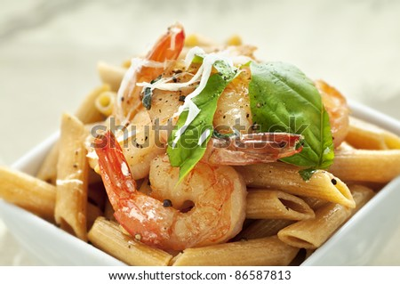 White square bowl of whole wheat pasta with sauteed shrimp and basil/Pasta with Shrimp - stock photo